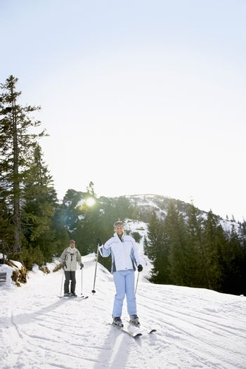 Couple skiing down slope