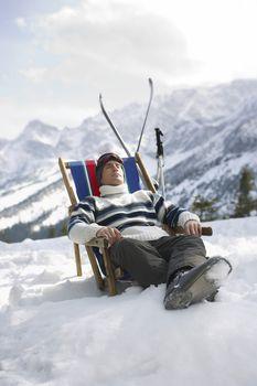 Skier resting in deckchair in mountains