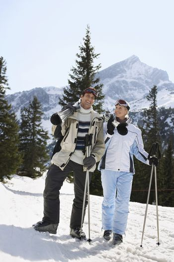 Skiing couple standing carrying skis on shoulders on ski slope