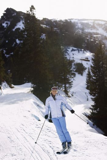Full length of a woman skiing down slope