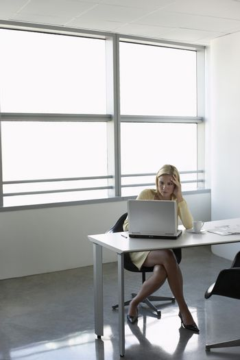 Young businesswoman using laptop at office desk