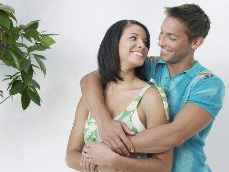 Affectionate young man embracing woman from behind