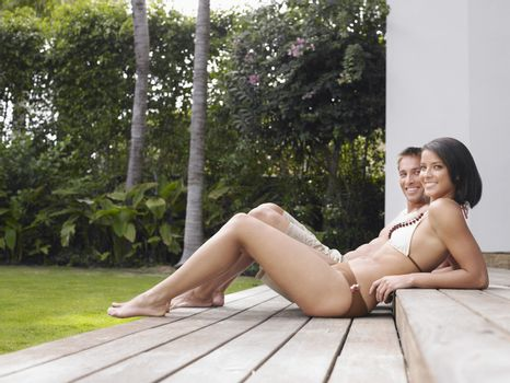 Full length side view of a semi dressed young couple relaxing outdoors