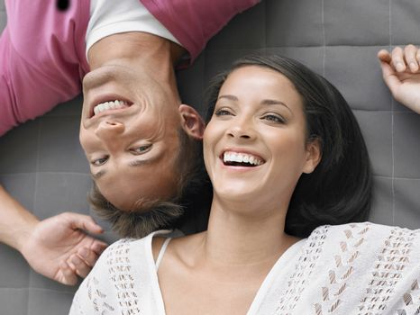 Elevated view of a cheerful young couple lying down