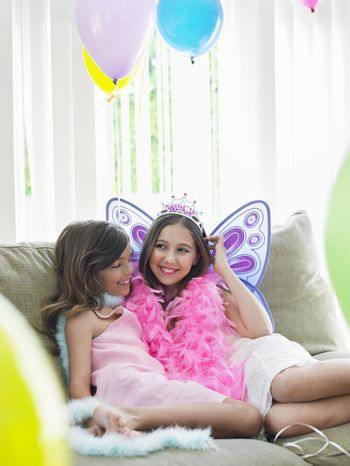Portrait of two happy young girls sitting on sofa in party costumes