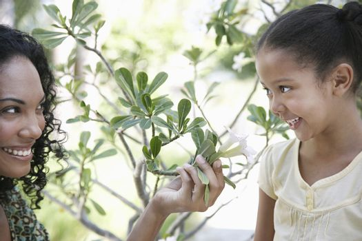Happy mother showing flower plant to daughter in garden