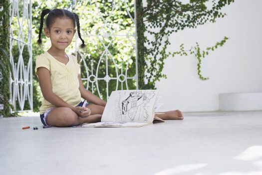 Girl (5-6 years) sitting on porch and drawing