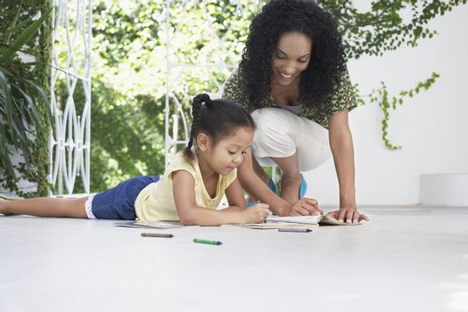 Smiling mother and daughter drawing with crayons on porch