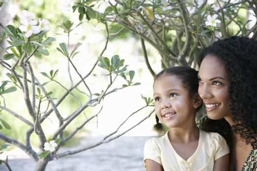Happy mother and daughter looking at flower plant in garden