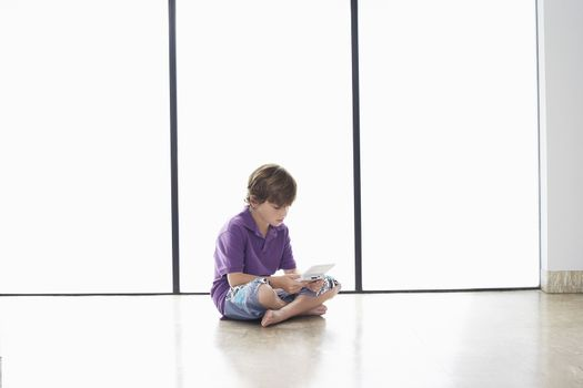 Full length of young boy playing handheld video game on floor