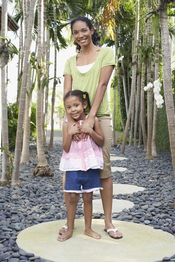 Full length of mother standing with arm around daughter on stepping stone