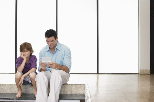Happy father playing handheld video game sitting next to son at home