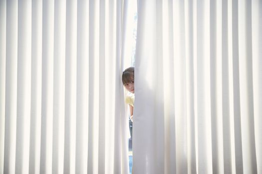 Portrait of little girl peeking from curtains at home