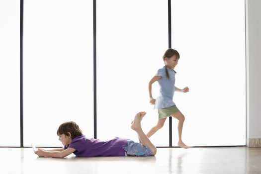 Full length of young boy playing handheld video game on floor while sister running around