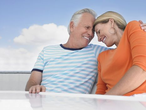 Romantic middle aged couple with arm around on yacht