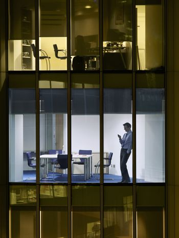 Young businessman text messaging late night in office