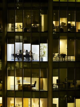 Business meeting viewed through illuminated window of office block at night