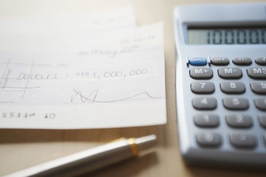 Calculator, pen and filled cheque on wooden table