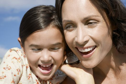 Mother and daughter heads together using mobile phone head and shoulders