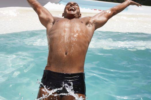 Cheerful young man diving backward into swimming pool