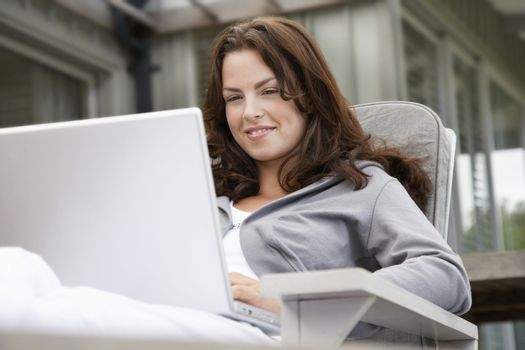 Beautiful young woman using laptop on porch