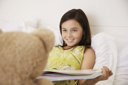 Happy girl reading story book to her teddy bear in bed