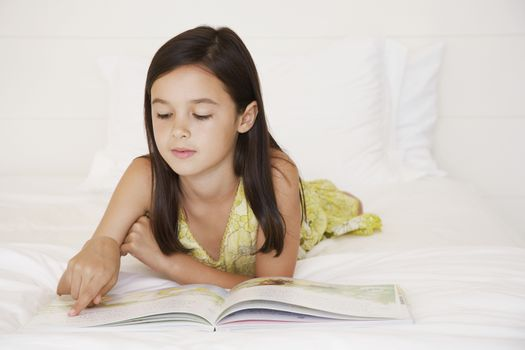 Little girl reading story book in bed