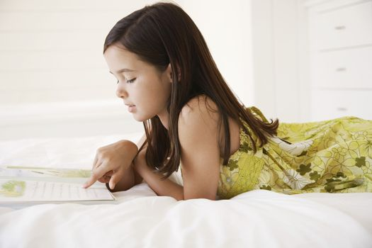 Side view of little girl reading story book in bed