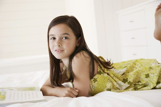 Portrait of little girl with story book in bed