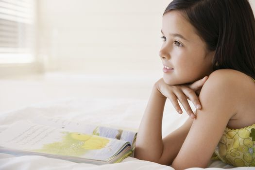 Happy little girl daydreaming while reading story book in bed