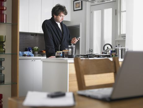 Man standing in kitchen text messaging laptop on table in foreground