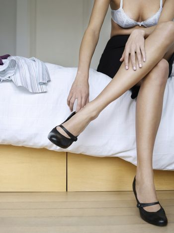 Low section of semi dressed woman putting on shoes in bed