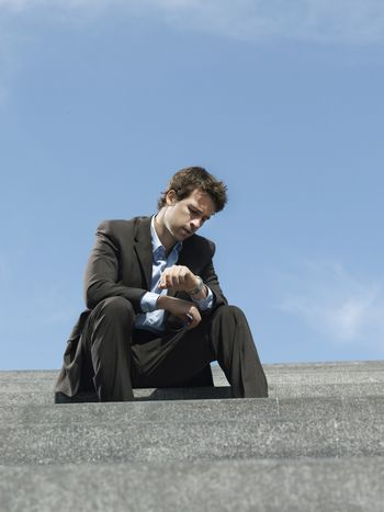 Young businessman sitting on steps looking at wristwatch