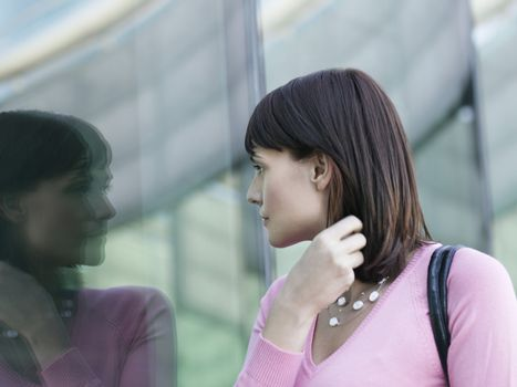 Young businesswoman looking at reflection of self in window