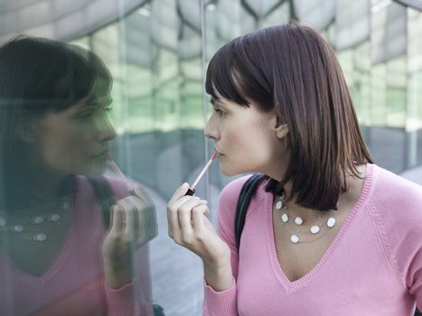Young woman applying lip gloss while looking at reflection of self in window