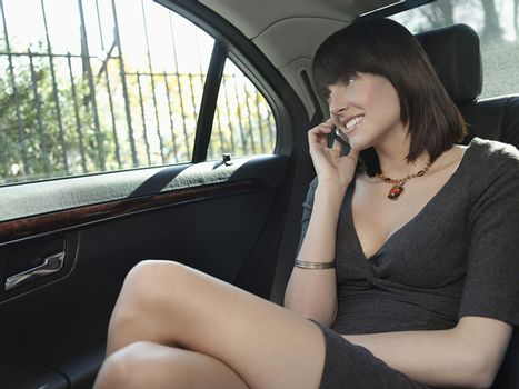 Young businesswoman using mobile phone in back seat of car