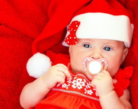 Newborn girl wearing Santa hat