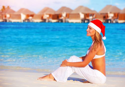 Beautiful young woman celebrating Christmas holiday on Maldive island, wearing red Santa hat, sitting on the beach, luxury resort