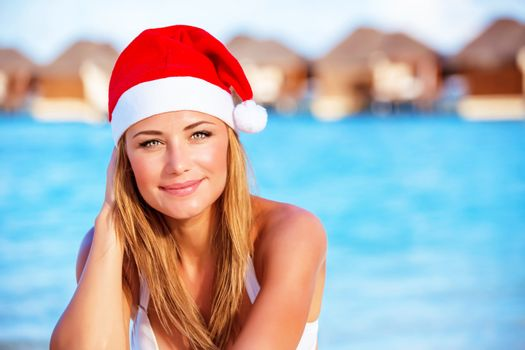 Closeup portrait of attractive blonde female wearing red Santa hat celebrating Christmas holidays on Maldives, exotic travel and vacation concept