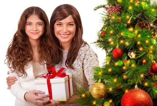 Christmas celebration at home, young mother with daughter having fun near beautiful decorated Xmas tree, receive present, happy holidays concept