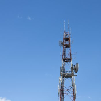 Red and white roof top cellular tower under blue sky