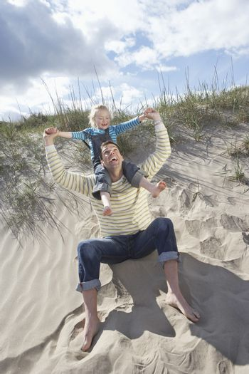 Girl (5-6) on fathers shoulders at beach