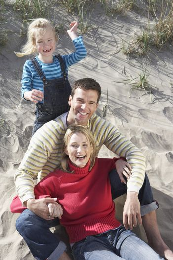Portrait of cheerful parents with daughter on sandy beach