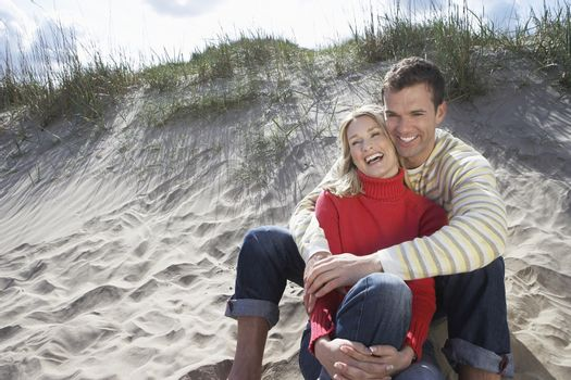 Cheerful couple embracing on sandy beach
