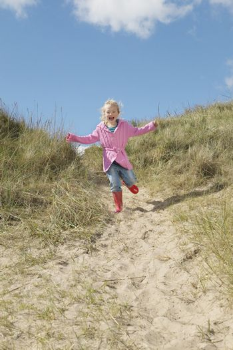 Girl (5-6) running down sand dunes