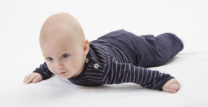cheerful baby trying to get around. horizontal image, studio shot