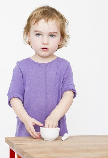 young girl standing behind desk . Studio shot with grey background