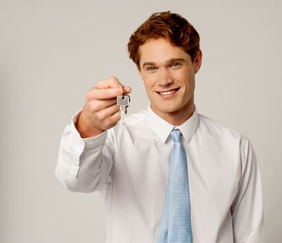 Smiling corporate holding a key
