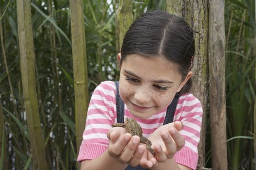 Happy young girl looking at toad in front of fence