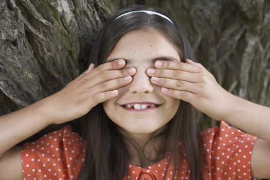 Closeup of happy girl playing hide and seek while covering eyes by tree